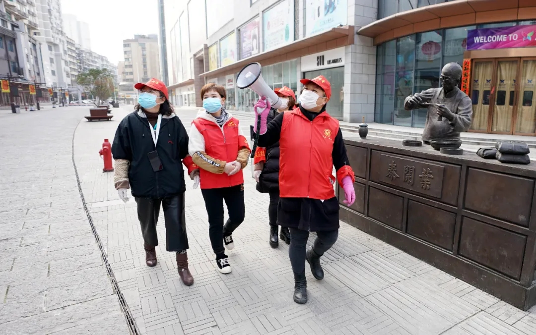 2月13日,武汉市汉正街石码社区党委书记兼居委会主任韩小琴(右一)率领社区事情职员向步行街旁的住民宣传防疫常识。 新华社记者 王毓国 摄