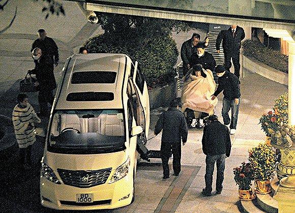2011年2月5日晚上,何鸿燊离开四姨太家,由看护和保镖护送上车。
