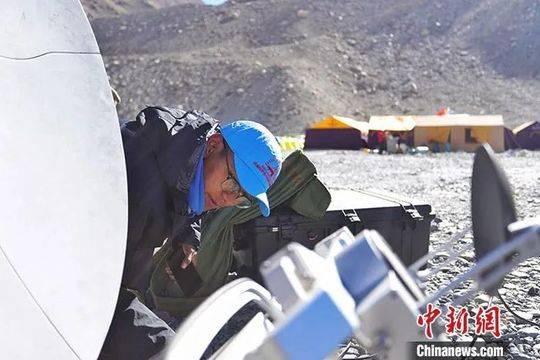 24日,在西藏日喀则市定日县珠峰(珠穆朗玛峰)登山大本营,由西藏自治区气象局选派的预报服务团队成员在调试卫星天线。中新社发 洛桑 摄
