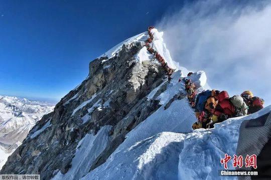 资料图:2019年,珠穆朗玛峰迎来数百名登山者。由于人数太多,通往山顶的路段出现拥堵及排队现象。图为数百名登山者在珠峰登顶之路上排队。