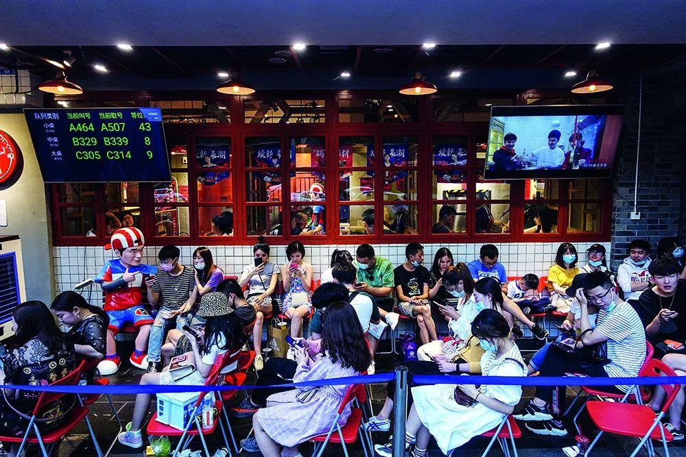 """5月3日,四川成都市东大街""""火锅一条街""""生意火爆,多家店外都有大批食客等候。图/人民视觉"""