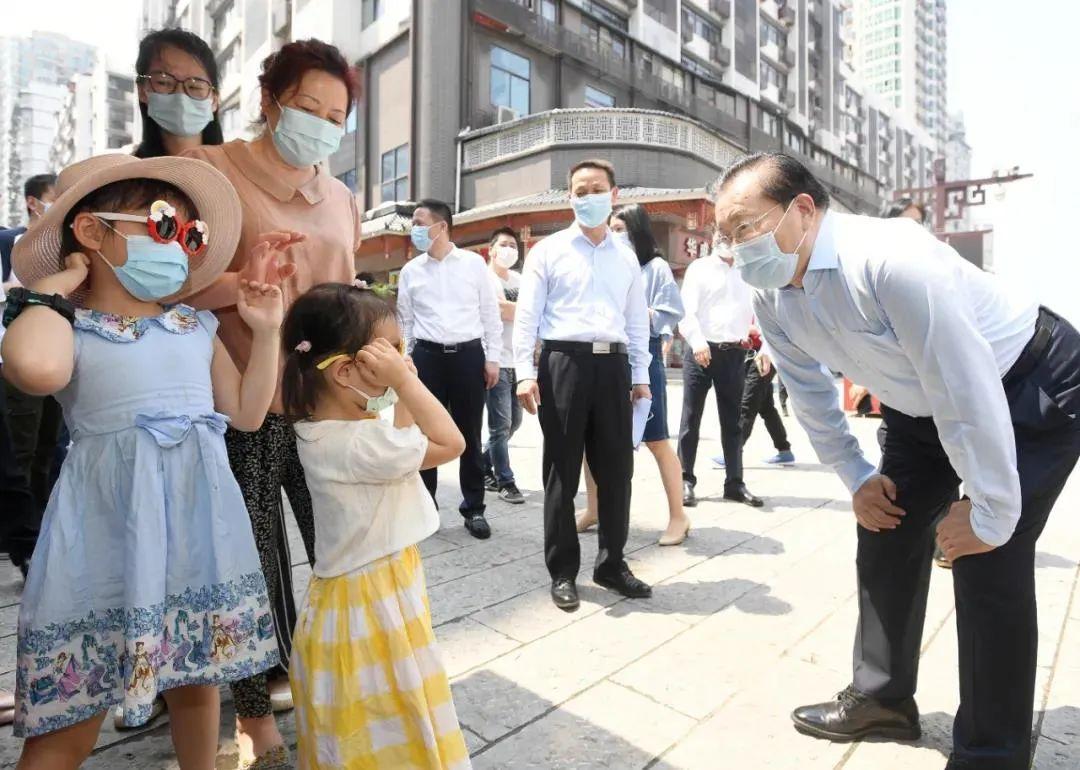 5月2日,汉正街,王忠林和小游客打招呼交谈。图/《长江日报》