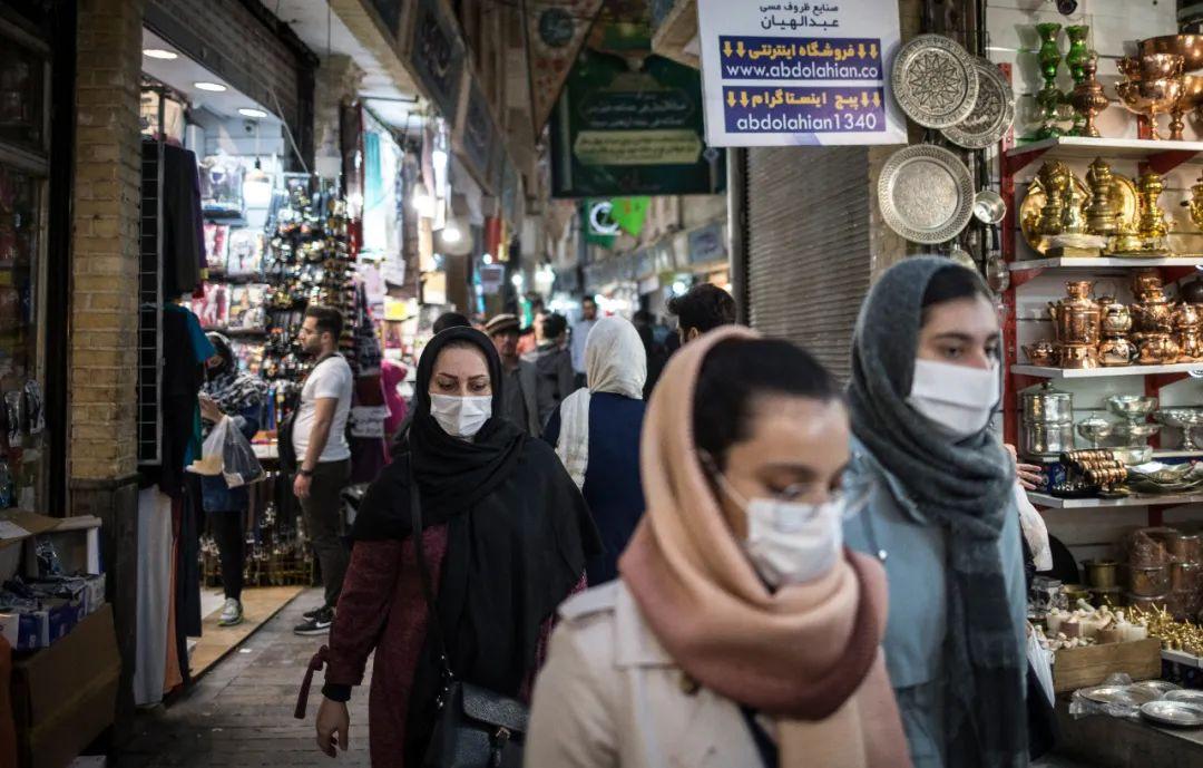 4月24日,在伊朗德黑兰,戴着口罩的市民经过集市。新华社发(艾哈迈德·哈拉比萨斯摄)