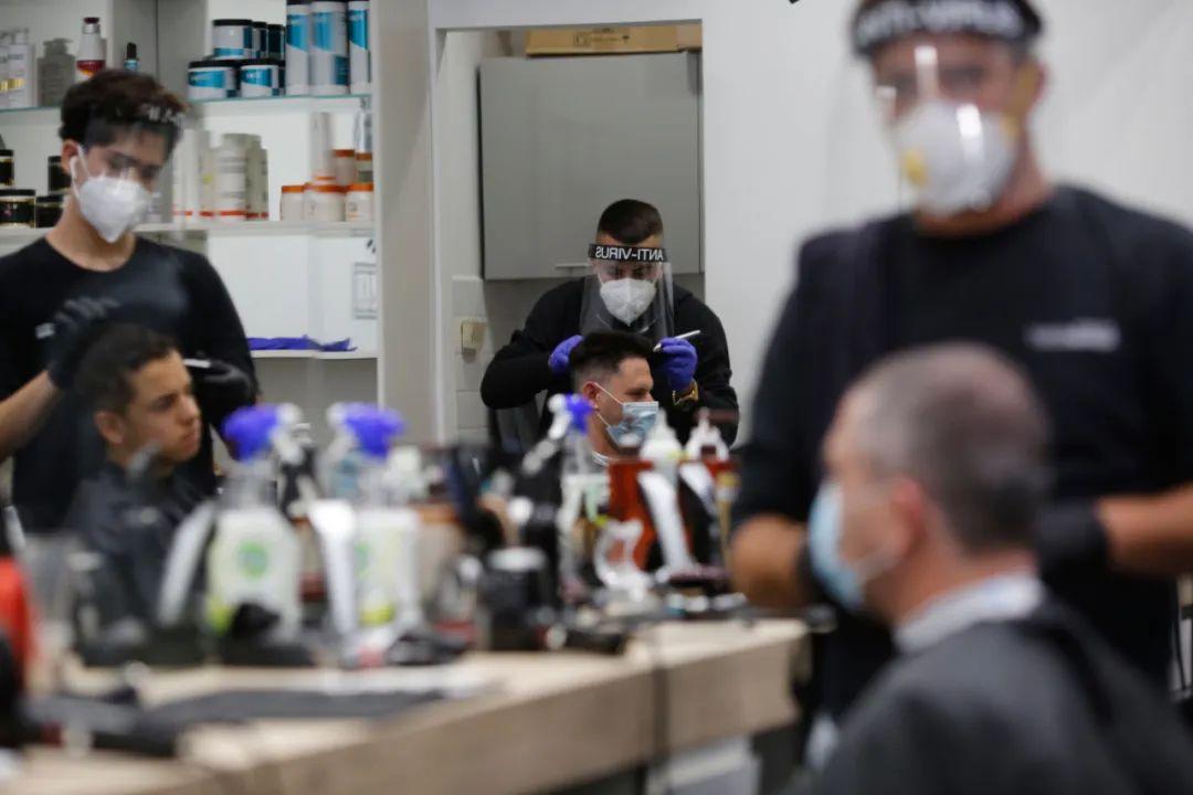 4月26日,在以色列中部城市莫迪因的一家理发店内,理发师在为客人理发。新华社发(吉尔·科恩·马根摄)