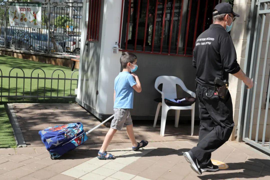 5月4日,在以色列中部城市佩塔提克瓦,一名小学生戴着口罩来到学校。新华社/基尼图片社