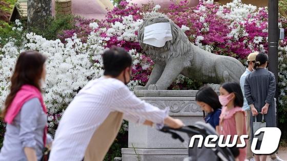 为宣传防疫知识,首尔一公园石狮子被戴上口罩。(news 1)
