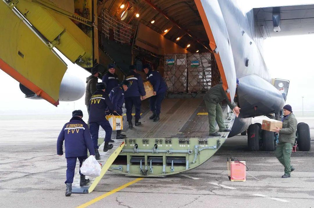 ↑2020年2月12日,在乌兹别克斯坦都城塔什干国际机场,乌方事情职员将第一批救济中国的物资搬上专机。新华社发