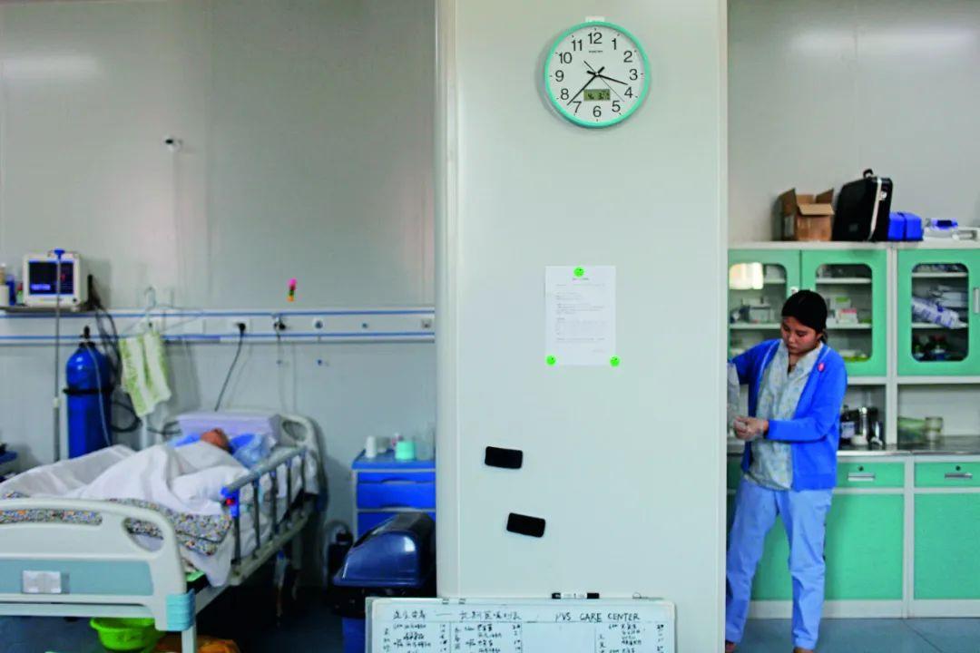 护士在病房内给病人预备食品。拍照/张涛