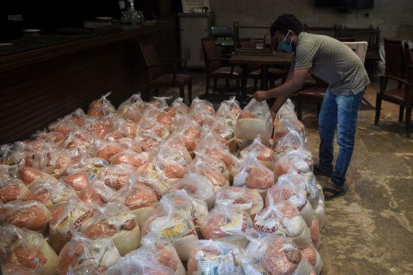 印度孟买一名工作人员8日清点准备分发的救济食品。法新社