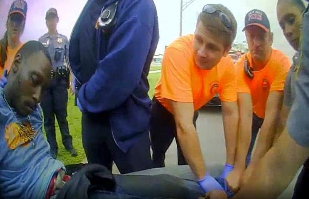 黑人男子斯科特昏迷后,被警察和医护人员抬上担架。(美联社)