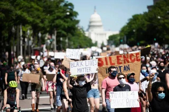 5月30日,在美国首都华盛顿国会山附近,人们手持标语参加抗议活动 摄 |刘杰(新华社)