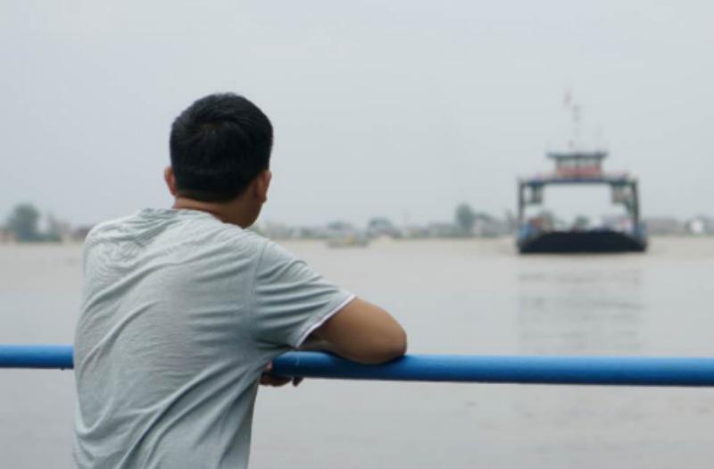 7月11日,一位江洲镇住民在渡船上隔江远眺江洲镇。中青报·中青网见习记者 李强 摄