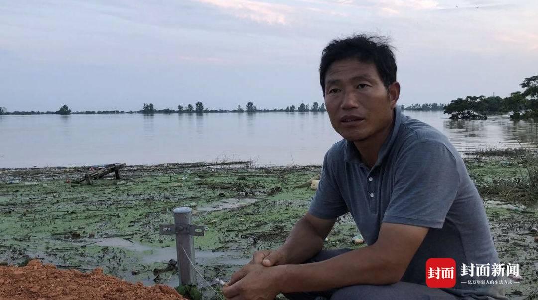 """双港镇双港村村支书彭俊英也不停服从在抗洪一线,他说 """"人在堤在""""。。他的家在水库卑鄙,大水水位线已经高过家里的房顶。"""