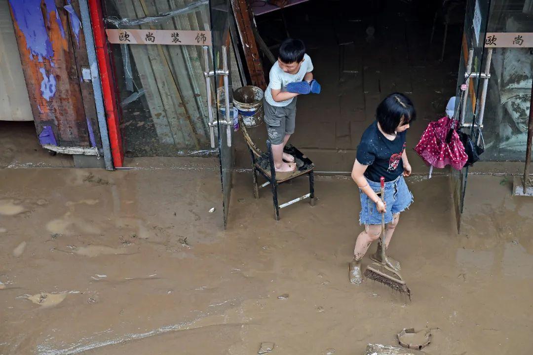 7月7日,歙县的居民在清理淤泥。图/人民视觉