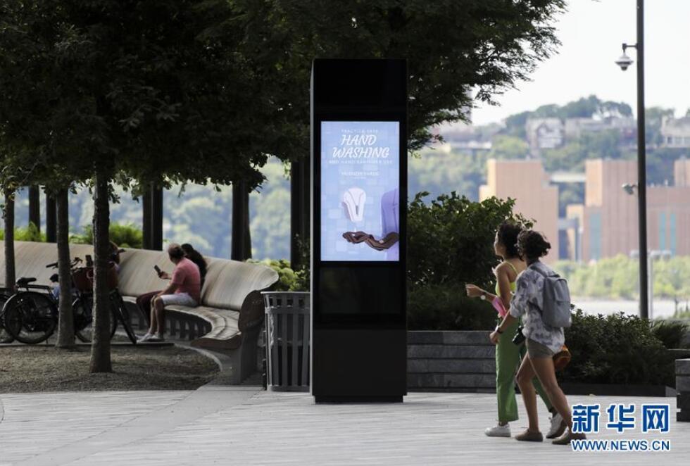 7月14日,在美国纽约一家尚未恢复店内购物的购物中心外,电子屏介绍正确洗手的方式。图丨新华社