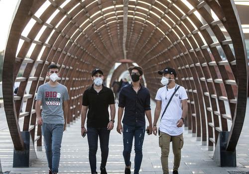 7月5日,人们佩戴口罩在伊朗首都德黑兰街头走过。新华社发(艾哈迈德·哈拉比萨斯 摄)