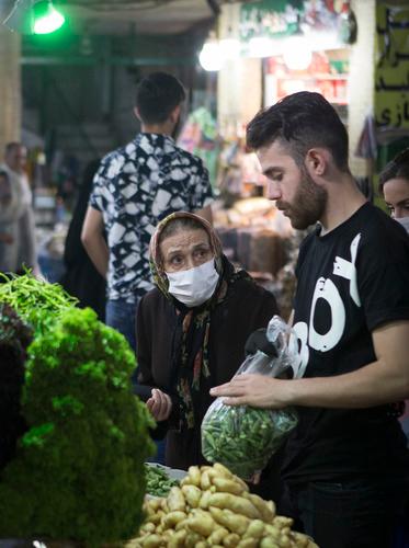 6月23日,一名佩戴口罩的老人在伊朗德黑兰购买蔬果。新华社发(艾哈迈德·哈拉比萨斯摄)
