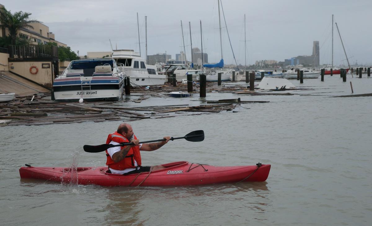 """在""""汉娜""""袭击私人游艇码头后,诺兰(John Nolan)划皮艇去调查船只受损情况。他的船和其它约30艘船在风暴中丢失或损坏。"""