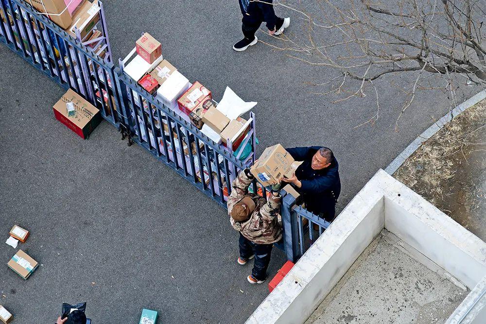 3月2日,北京一小区门口,人们隔着栅栏交代快递件。图/人民视觉