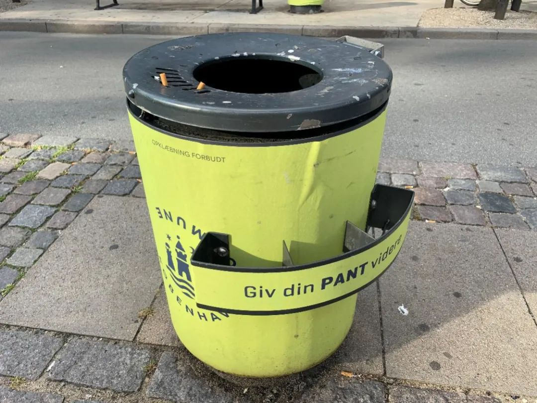 """哥本哈根街头的垃圾桶,上面丹麦语的意思是""""把空瓶留给需要的人""""。新华社发(于珂 摄)"""