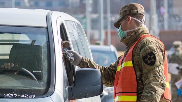驻韩美军士兵对出入人员测量体温(KBS新闻)