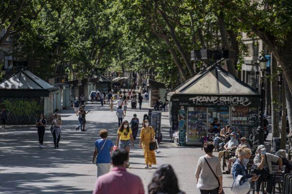 6月25日,人们在西班牙巴塞罗那兰布拉大道散步。(新华社)