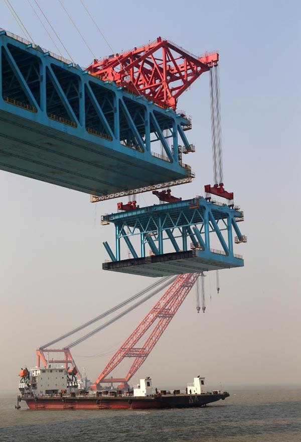 图為施工职员在進行沪苏通长江公铁大桥主航道桥28号墩的大节段钢梁悬吊。(新華社 丁晓春 摄)
