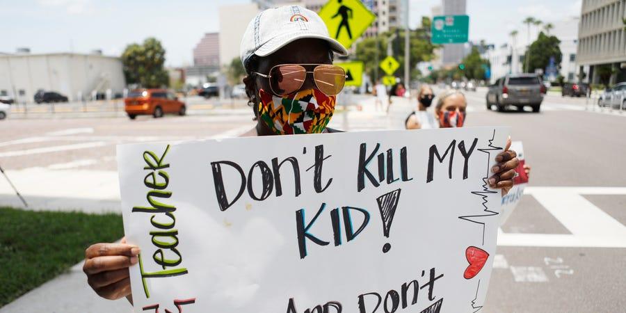 """一名教育工作者抗议白宫强推线下授课,标语为""""别杀害我的孩子""""。(图源:Getty Images)"""