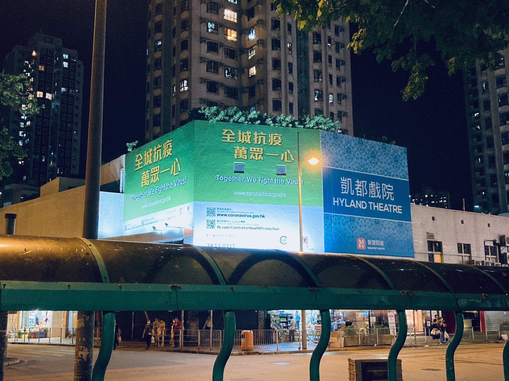 """香港新确诊的""""再感染""""病例或许证明了新冠肺炎患者在康复后可能也并非""""一世免疫"""",因此不能掉以轻心,要继续防疫措施。图为香港某区内刊登的政府呼吁""""全城抗疫、万众一心""""的广告牌。《财经》记者 焦建/摄"""