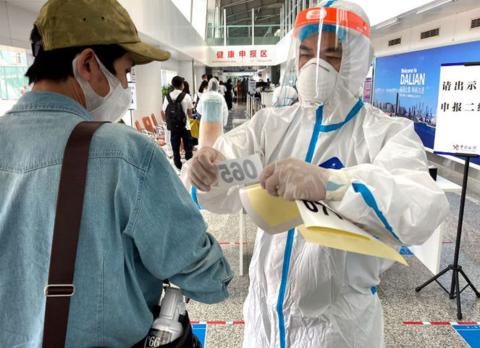 ▲刚下飞机,工作人员就在记者手臂贴上号码牌(西日本新闻)