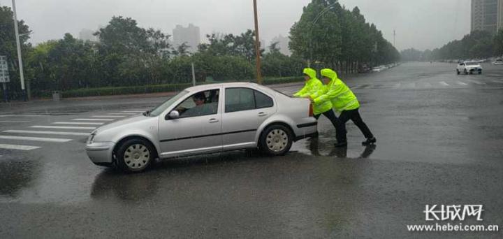 执勤民警冒雨为群众手推车。通讯员黄鹏供图