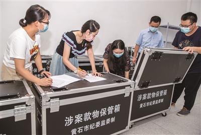 图为湖北省黄石市纪委监委检察观察职员移交挂号暂扣的涉案物品。何戈 摄
