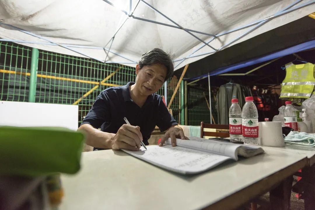 校党委书记高翅查抄巡防日记并在日记末了壹頁具名(刘涛 摄)