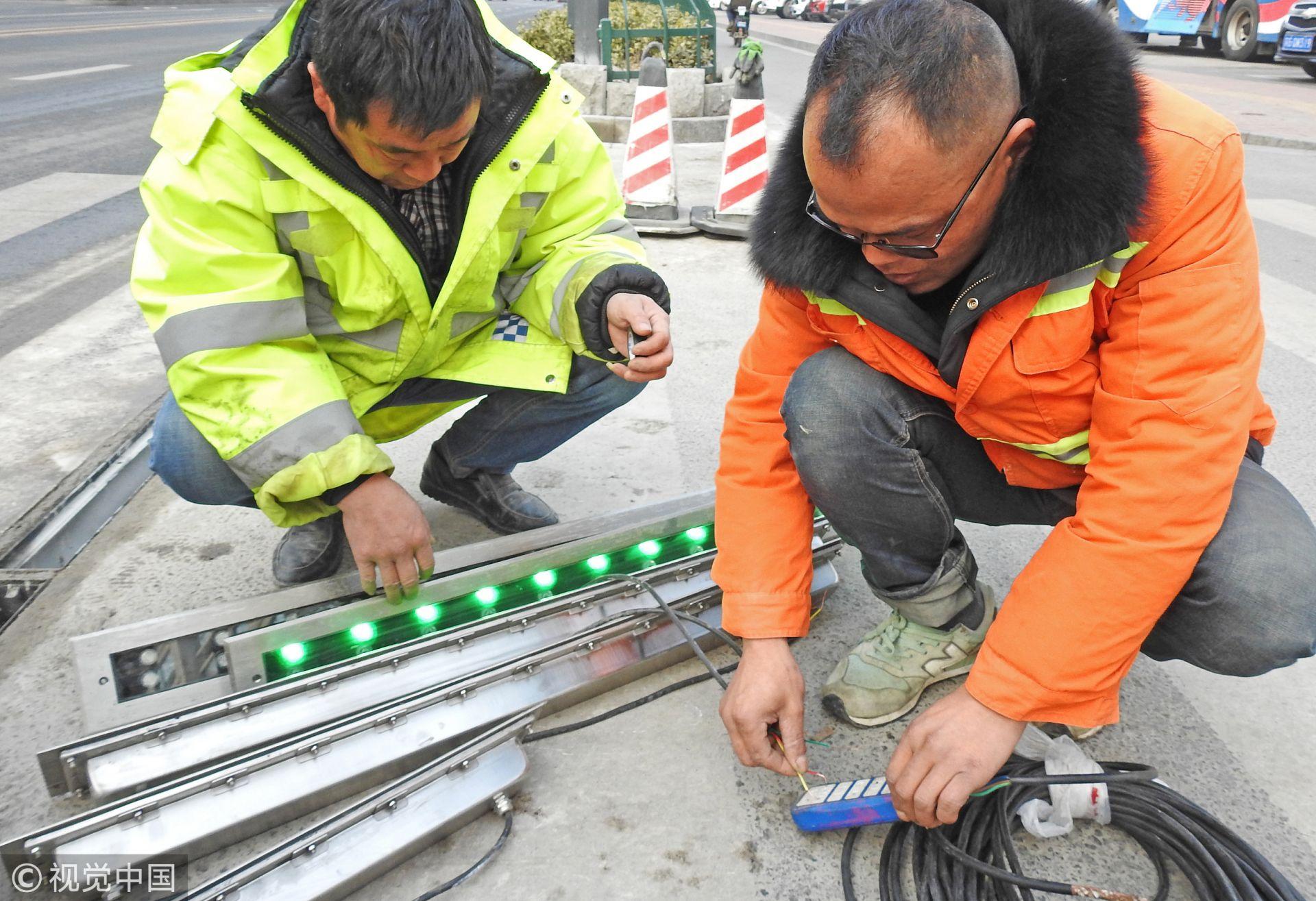 江苏连云港,工人正在安装和调试地埋式智能斑马线系统