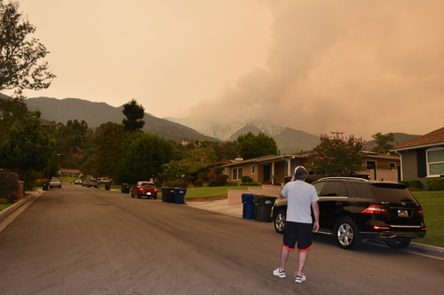 9月10日,在美国洛杉矶县蒙罗维亚,一名男子望向安杰利斯国家森林公园燃烧的山火。新华社记者 高山 摄