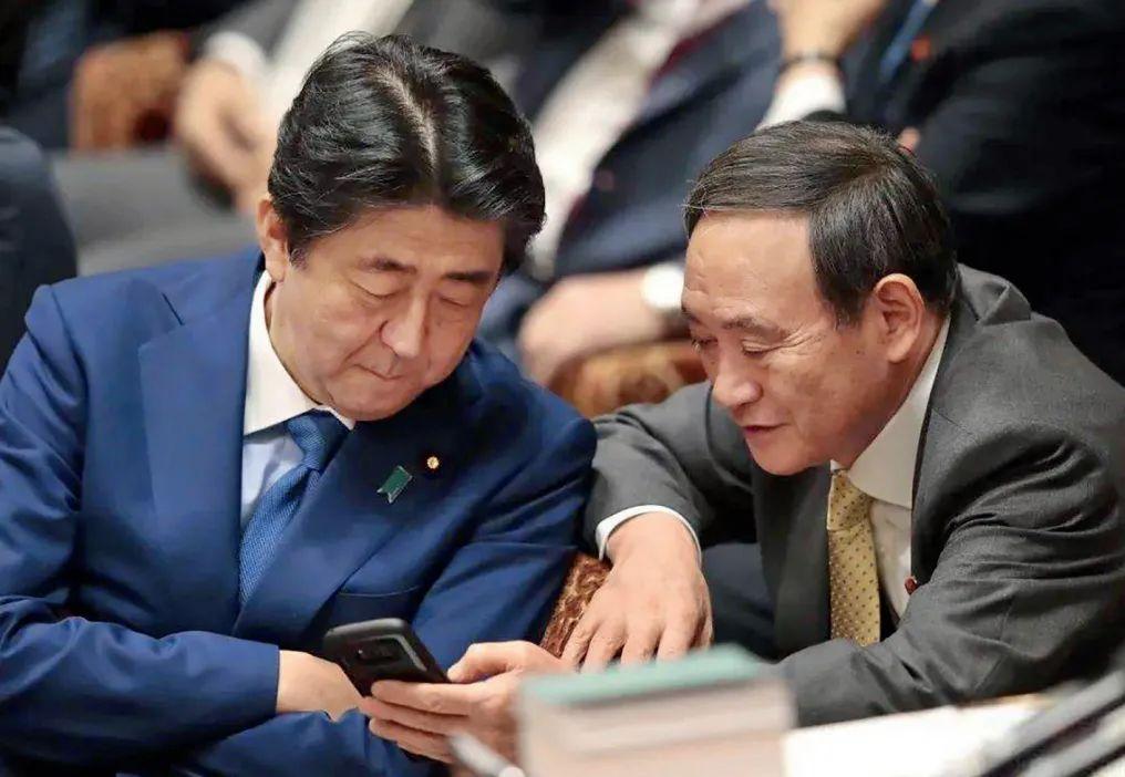·安倍晋三(左)与菅义伟在会议上讨论。