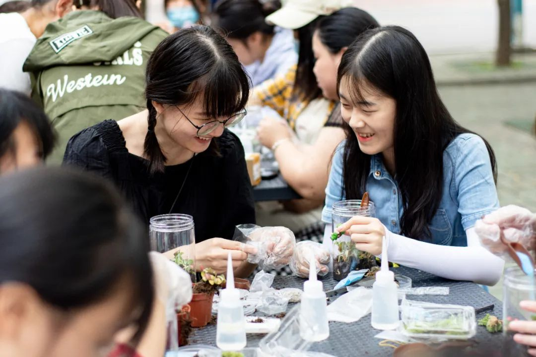 ▲新生欧倩茵在和她的同砚建造生态瓶的历程中有说有笑 (彭雨格 摄)