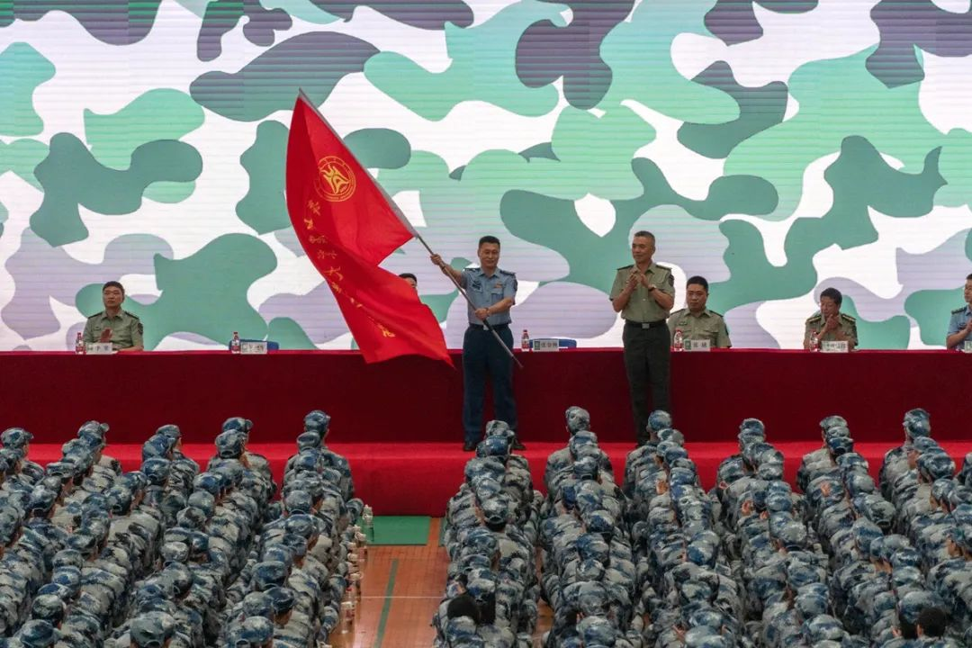 ▲张金洲为军训师授旗(徐伟康 摄)