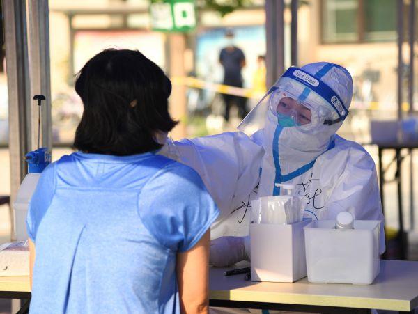 中国制定了严密的措施防控疫情。图为6月23日,在北京市海淀区八里庄街道的一处核酸检测采样点,医护人员(右)为居民进行咽拭子采样。(任超 摄)