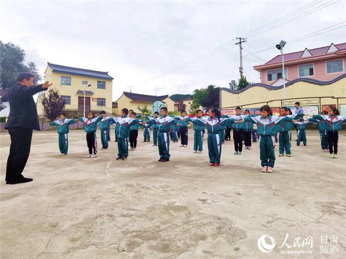 红崖村小学门前的文化广场,孩子们正在上体育课。(高翔 摄)