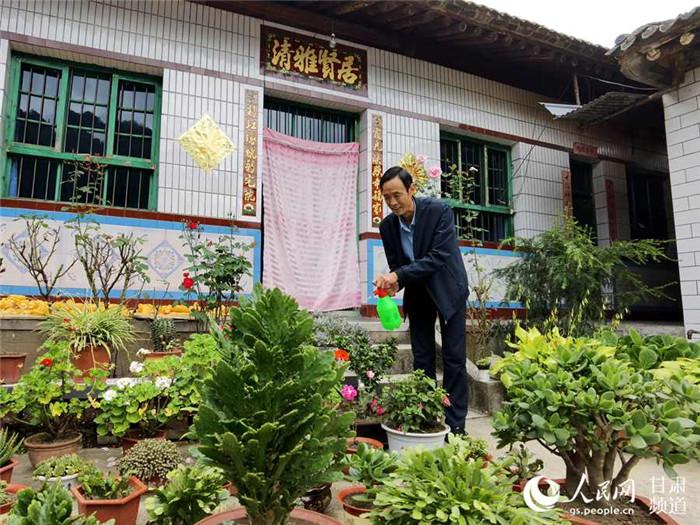 刘成平正在给院里的绿植浇水。(高翔 摄)