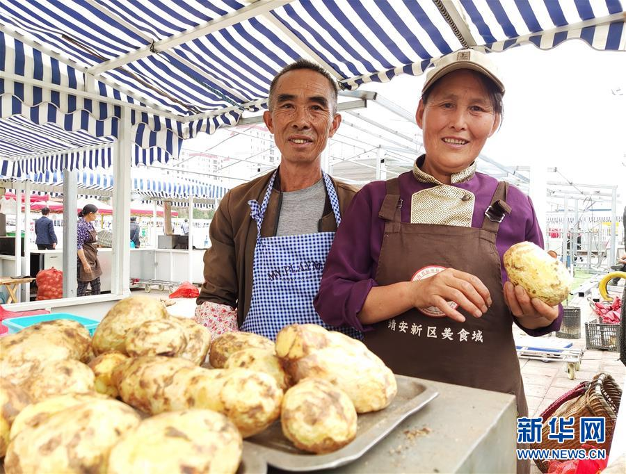 云南省昭通市靖安新区的搬家群众祁仕清(右)与老伴鲁洪凯在安顿区广场上卖烤洋芋(8月8日摄)。 记华社新者。 林碧锋 摄
