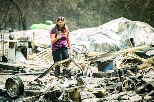 ▲8月23日,美国加利福尼亚州瓦卡维尔的居民在山火过后留下的废墟中捡拾个人物品。|新华社发