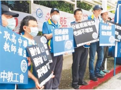 """在近期举办的台湾高中及特殊教育学校北区校长会议会场外,部分高中职教师代表举牌抗议""""新课纲""""令教师过劳状况日益加剧。  资料图片"""