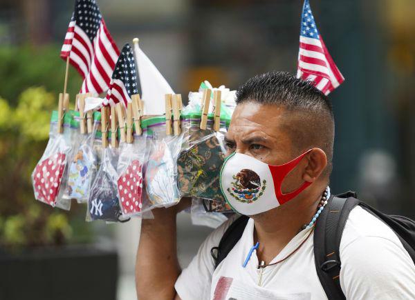 8月19日,一名小贩在美国纽约时报广场售卖口罩。新华社