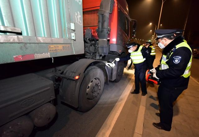 (机动车特别是柴油车已经成为许多大中城市的首要污染源。图为环境监察人员在夜查柴油货车。摄影/章轲)