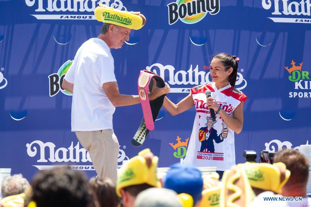 New York City Mayor Bill de Blasio (L) hands a trophy belt to women's competition champion Michelle Lesco during a hot dog eating contest in New York, the United States, on July 4, 2021. Defending champion Joey Chestnut broke his own world record Sunday by devouring 76 hot dogs in 10 minutes at the contest. Michelle Lesco won the women's title by eating 30.75 hot dogs in 10 minutes. (Xinhua/Michael Nagle)