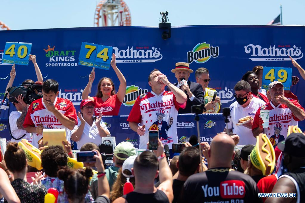 Joey Chestnut (C) competes in a hot dog eating contest in New York, the United States, on July 4, 2021. Defending champion Joey Chestnut broke his own world record Sunday by devouring 76 hot dogs in 10 minutes at the contest. Michelle Lesco won the women's title by eating 30.75 hot dogs in 10 minutes. (Xinhua/Michael Nagle)