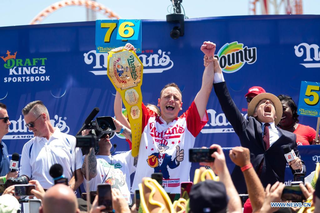 Joey Chestnut (C) celebrates after defending his men's championship title in a hot dog eating contest in New York, the United States, on July 4, 2021. Defending champion Joey Chestnut broke his own world record Sunday by devouring 76 hot dogs in 10 minutes at the contest. Michelle Lesco won the women's title by eating 30.75 hot dogs in 10 minutes. (Xinhua/Michael Nagle)