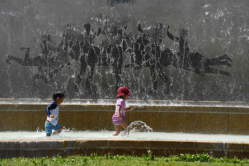 △高温下孩子们在喷泉边玩耍